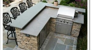 Outdoor fieldstone kitchen featuring raised stone bar counter, grill, refrigerat...