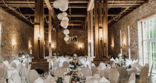 Wunderschöne Location für die Hochzeitsfeier mit runden Tischen in einem rusti...